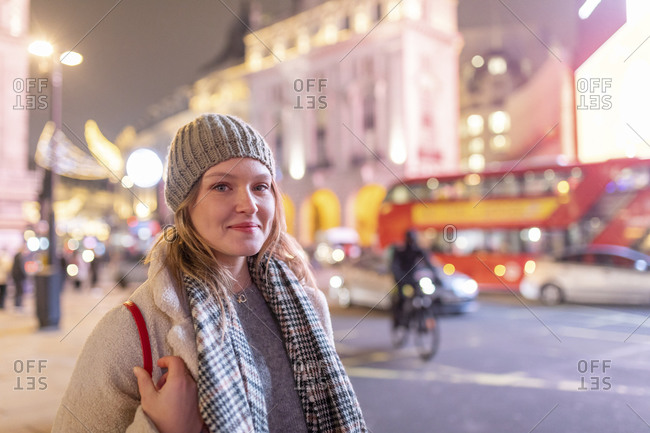 Young woman wearing warm clothing standing in Piccadilly Circus at night
