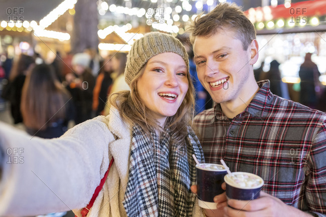 Happy couple holding hot chocolates while standing in illuminated Christmas market at night