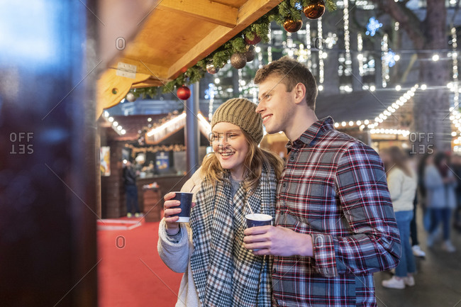 Couple enjoying hot chocolates in Christmas market at night