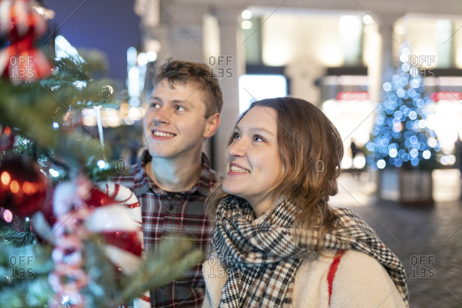 Happy young couple looking at Christmas tree and lights while standing in city