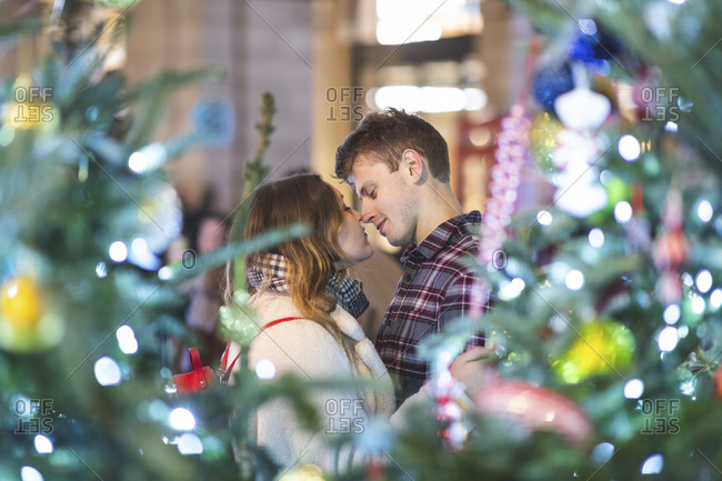 Young couple romancing while standing by illuminated Christmas tree at night