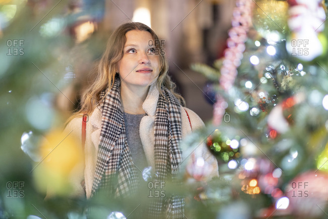 Young woman looking at illuminated Christmas tree and lights in city