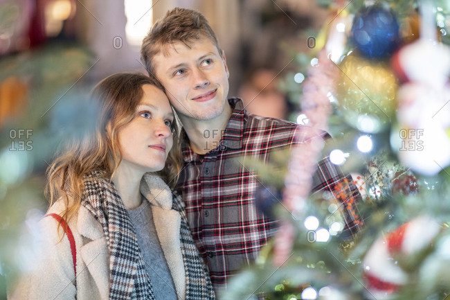 Loving young couple looking at Christmas tree and lights in city