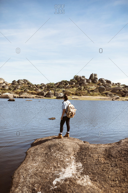 Woman with backpack admiring a beautiful rocky landscape of los barruecos in spain