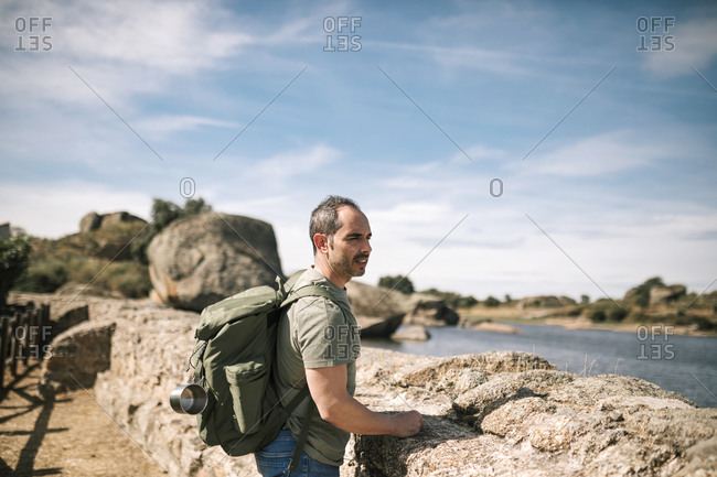 Young man with backpack looking at a landscape