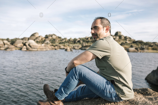 Young man sitting on a rock in nature