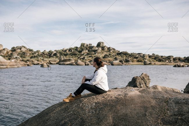 Young woman sitting on a rock in nature looking at a beautiful landscape