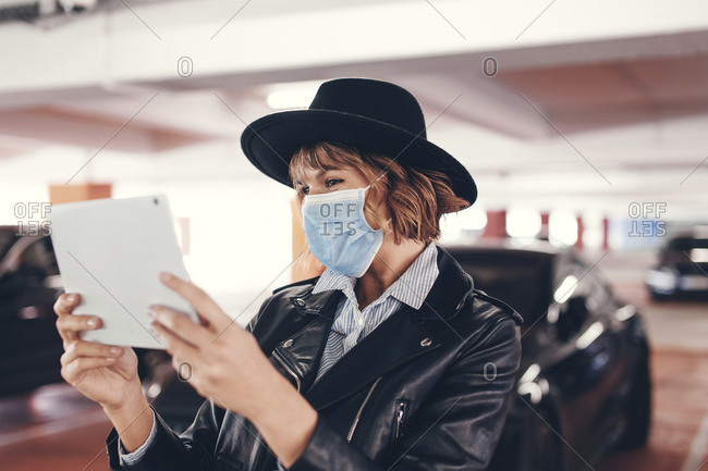 Young urban woman in mask and hat using tablet.