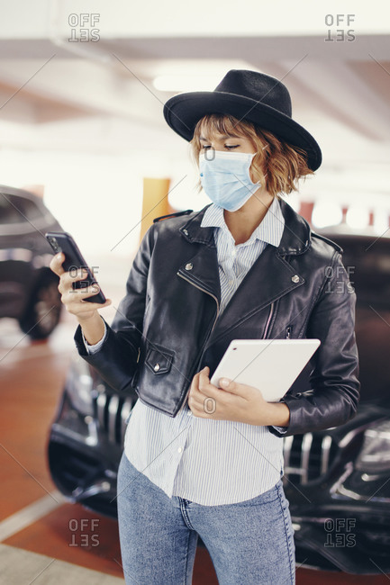 Young urban woman in mask texting by phone during pandemic.