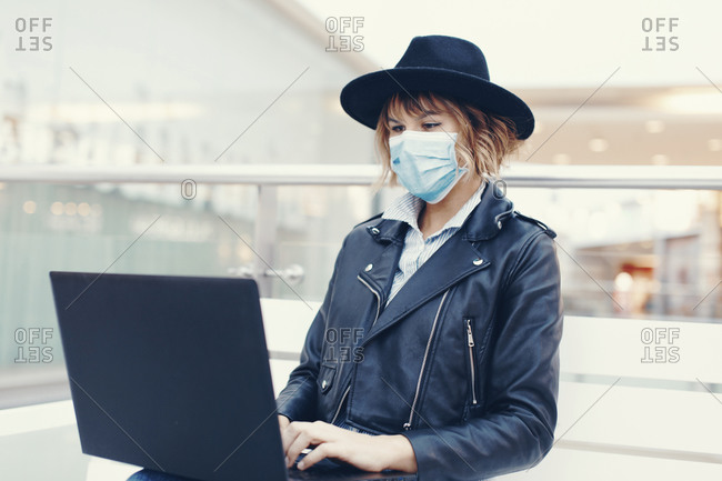 Trendy woman in mask using laptop indoors.