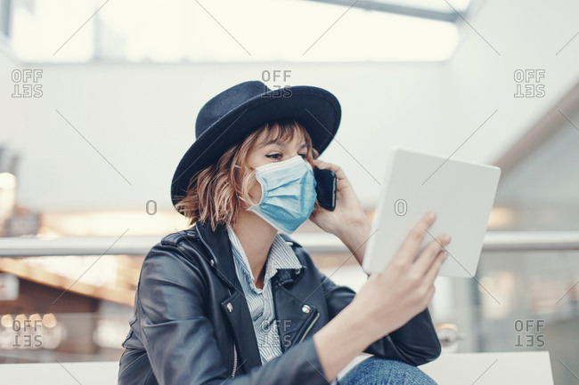 Young busy woman in mask using tablet while calling indoors during pandemic.