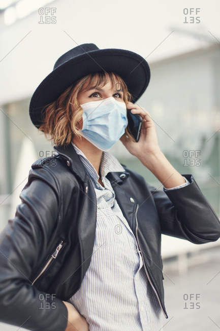Young stylish urban woman in mask calling indoors during pandemic.