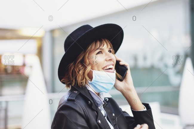 Young excited urban woman with mask down calling indoors during pandemic.