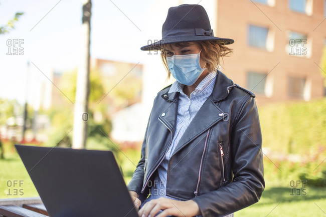 Young woman in mask using laptop outdoors in park during pandemic.