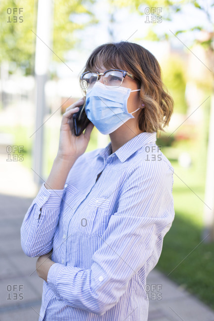 Young businesswoman in mask and eyeglasses calling in park.