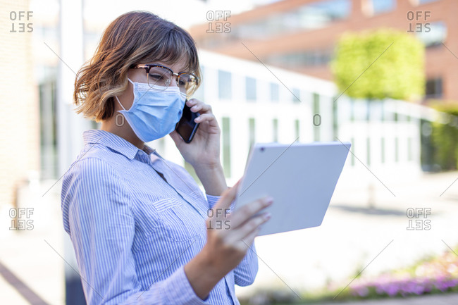 Young businesswoman in mask calling and reading from tablet outdoors in park.