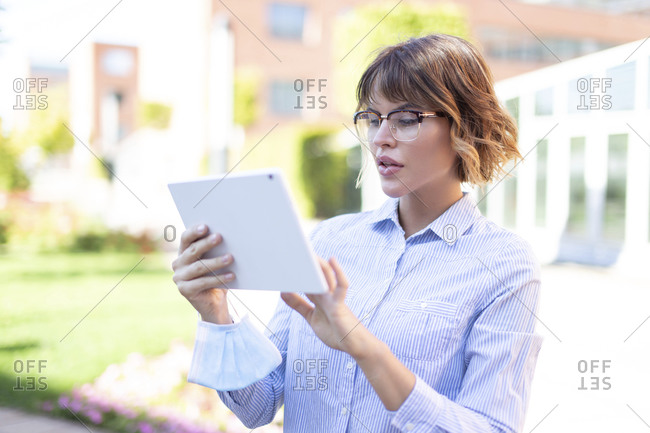 Young woman using tablet in park.