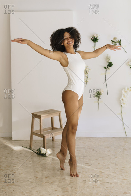 Happy black ballerina doing a classical pose.