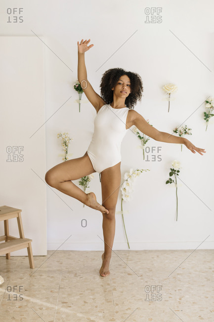 Black ballerina doing a classical pose in a studio with white flowers in the background.