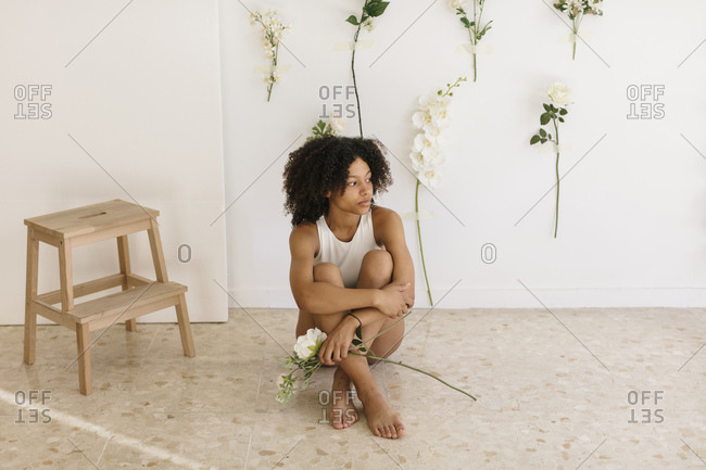 Ballerina sitting on the floor of a studio with flowers decorations. She is a black woman with white clothes.