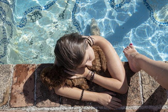 Overhead view of teen girl hugging dog on edge of swimming pool, Piandimeleto, Marche, Italy