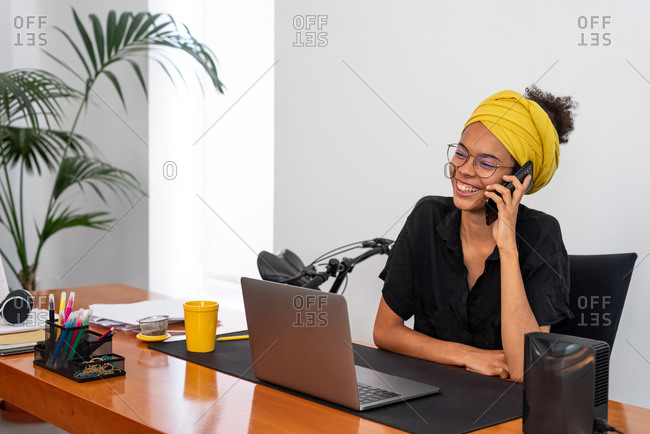 Shot of young Latin woman working at home office with laptop speaking on mobile phone
