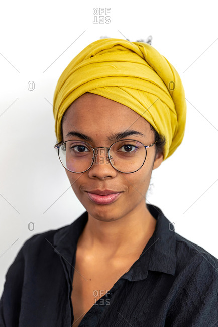 Close up of young mixed race woman with glasses and yellow scarf looking at camera while posing against white blank wall