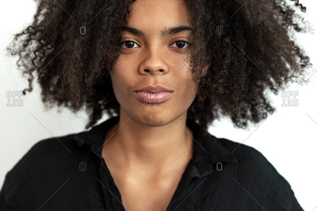 Close up of young mixed race woman looking at camera while posing against white blank wall