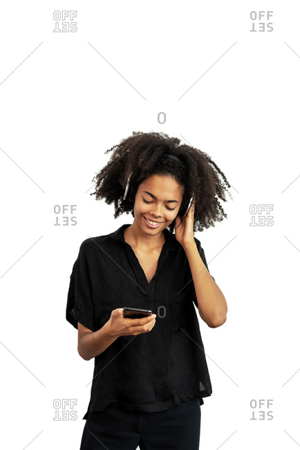 Young mixed race woman with headphones listening music on a phone while posing against white blank wall