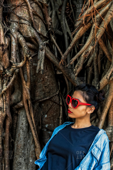 Asian Woman with a heart sunglasses in a tropical forest background