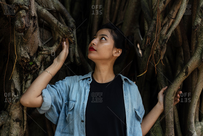Asian Woman with red lips in a tropical forest