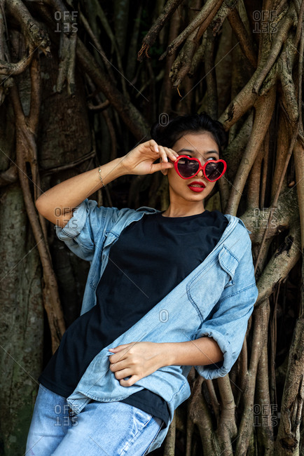 Asian Woman with a heart sunglasses in a tropical forest