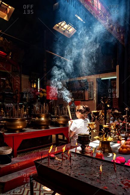 March 17, 22018: Woman praying in a Chinese temple of Kuala Lumpur, Malaysia