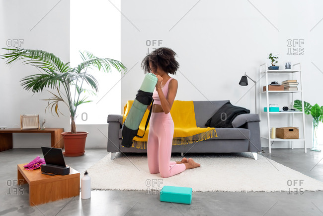 Afro woman unrolling her yoga mat at home