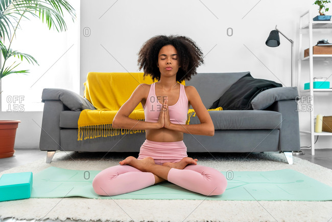 Afro-American woman practicing yoga lotus pose to meditation at cozy home