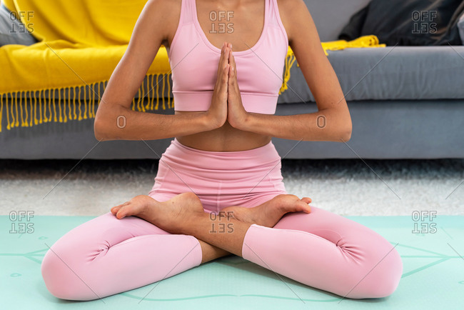 Cropped view of a woman practicing yoga lotus pose to meditation at cozy home