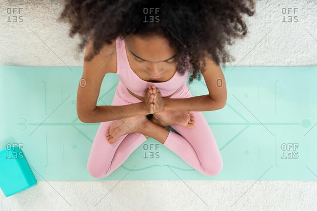 Afro woman practicing yoga lotus pose meditating at cozy home