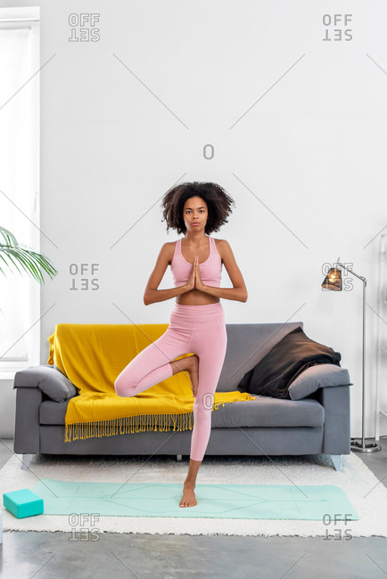 Afro American woman practicing yoga tree pose in cozy home