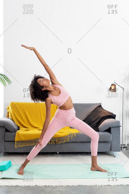 Afro woman doing the reverse warrior pose at home