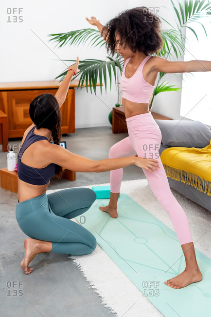 Yoga teacher correcting the Warrior II pose to her student at home