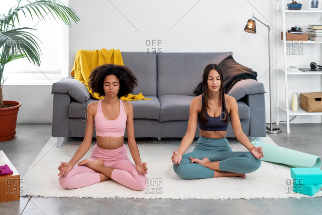 Two women practicing yoga lotus pose in cozy home
