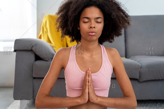 Afro American woman practicing yoga lotus pose in cozy home