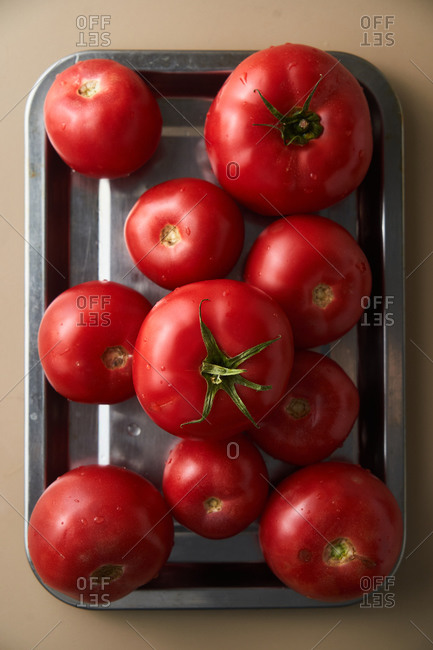 Freshly washed red tomatoes on metal dish