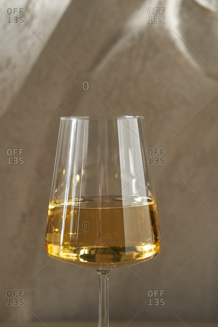 White wine in a glass in front of gray background