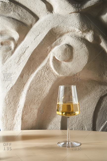 White wine in a glass in front of a textured background