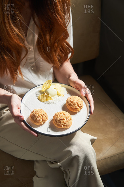 Woman with red hair holding a plate full of cookies