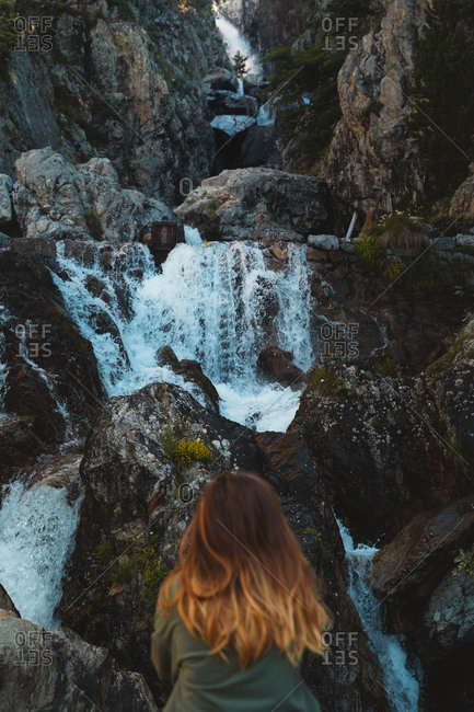 Blonde girl sitting on a rock in front of several waterfalls in Pyrenees on a sunny day