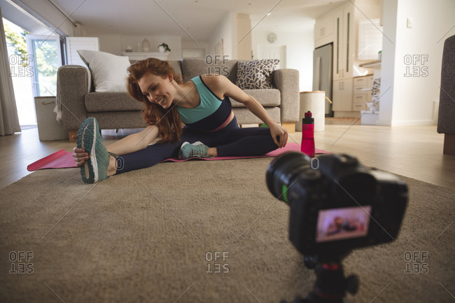 Caucasian woman spending time at home, in living room, exercising, stretching and recording it with a camera. Social distancing during Covid 19 Coronavirus quarantine lockdown.