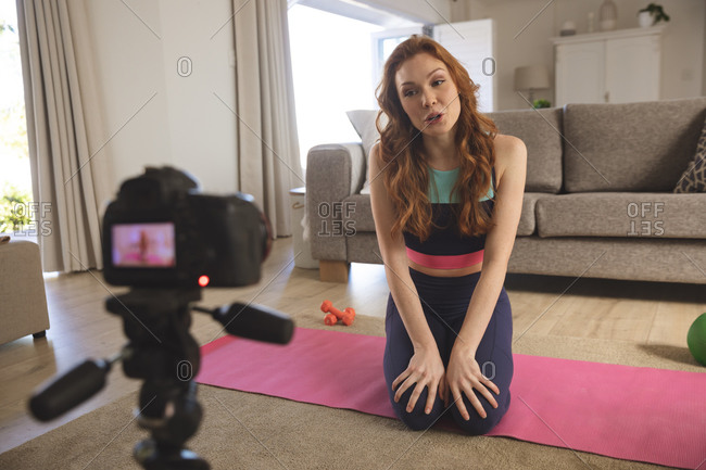 Caucasian woman spending time at home, in living room, exercising, talking and recording it with a camera. Social distancing during Covid 19 Coronavirus quarantine lockdown.