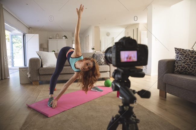 Caucasian woman spending time at home, in living room, exercising and recording it with a camera. Social distancing during Covid 19 Coronavirus quarantine lockdown.